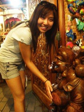 That's me rubbing a beautiful wooden buddha's tummy in a Malaysian street market in Kuala Lumpur.